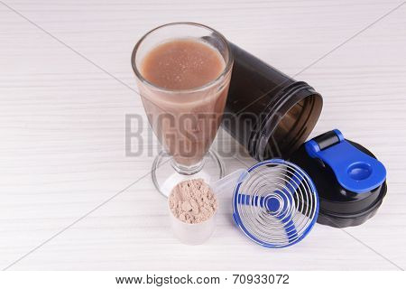 Whey protein powder with shake and plastic shaker on wooden background