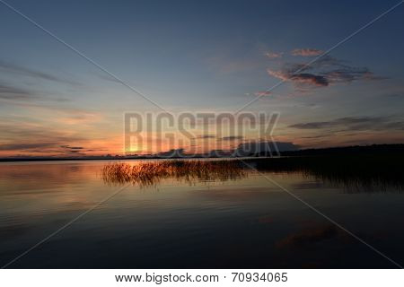Burgundy Sunset In The Blue Sky Over The Blue Water Surface Of The Lake With The Reflection Of Sunli