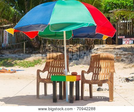 Table, chairs and colourful parasol on sandy beach in the tropics
