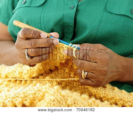 Close-up image of a senior woman's hands crocheting a gold-colored afghan.