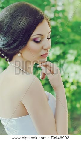 Beautiful bride with stylish make-up in white dress in spring garden