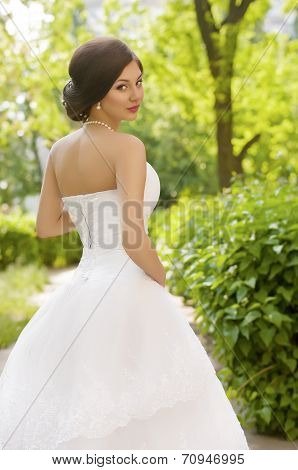 Beautiful bride in white dress in spring garden