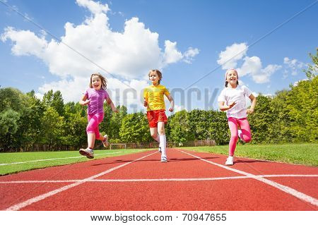 Smiling children running marathon together