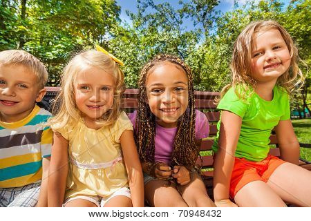Four kids on the bench in park