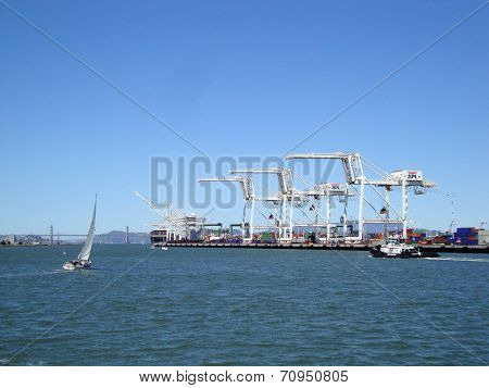Cargo Cranes, Tugboat And Sail Boat In Oakland Harbor On A Nice Day