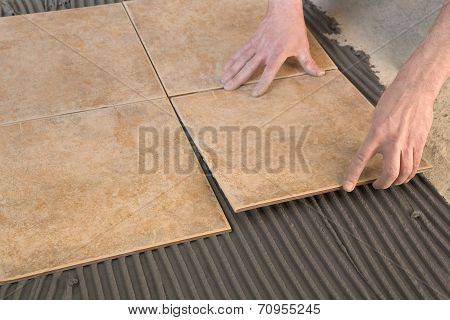 Master laid floor tiles on an adhesive tile