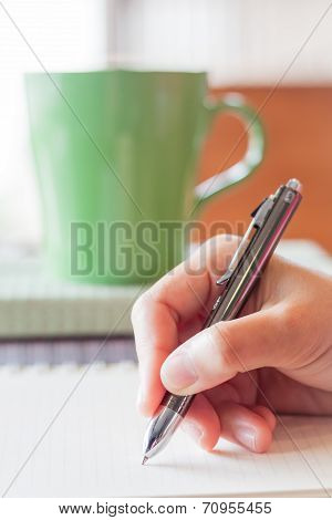 Hand Writing On Notebook In Coffee Shop