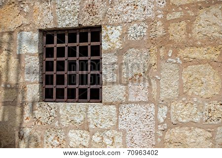 Window With Rusty Iron Bars At A Stone Wall