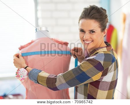 Portrait Of Happy Tailor Woman Working With Dress In Studio