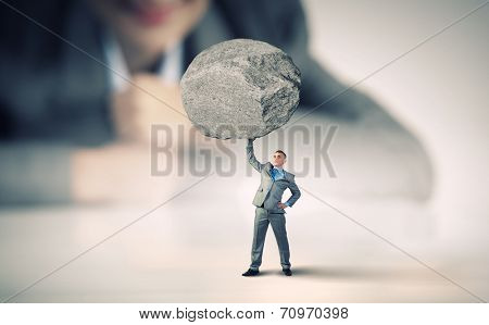 Businesswoman looking at miniature of businessman lifting stone above head