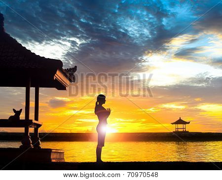 Woman Practising Yoga Meditation on Beach at Sunset or Sunrise