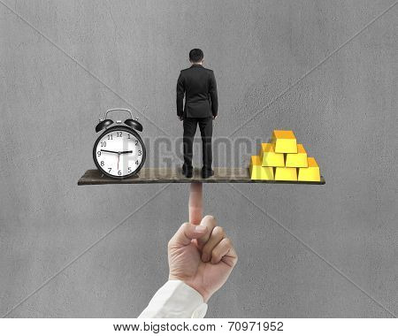Man Between Clock And Gold Balancing On Finger Seesaw
