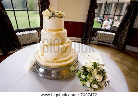 Wedding Cake Decorated With Roses And Gold Ribbon