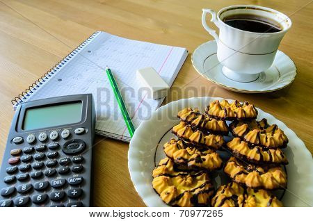 Workplace, Study Place With Calculator, Workbook, Cup Of Coffee And Cookies