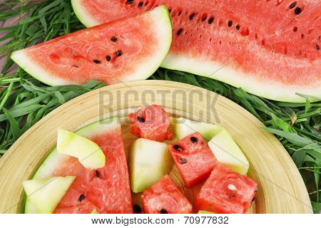 Water melon and melon on bamboo plate on grass background