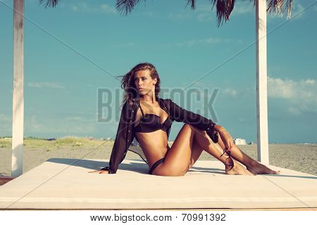 beautiful fashion woman posing on sandy beach in black bikini and shirt sitting on white beach bed under sunshade full body shot