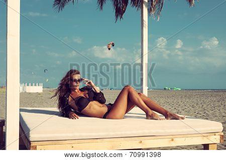beautiful fashion woman posing on sandy beach in black bikini and shirt lie on white beach bed under sunshade full body shot