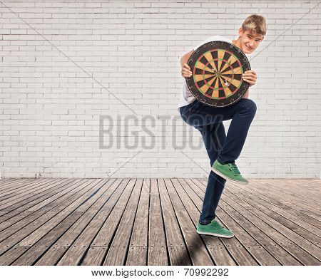 young man holding a dartboard on a room with white bricks wall and wood floor