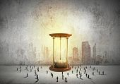 picture of hourglass figure  - Conceptual image with sandglass and silhouettes of business people around - JPG