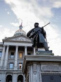 stock photo of granite dome  - Statue of solider in front of the State Capitol Dome in Denver Colorado shortly after sunrise - JPG