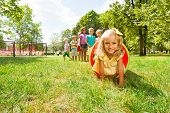 pic of crawling  - Kids play with tube on the lawn with little blond cute blond girl crawling out of pipe with smile and her friends standing in the queue - JPG
