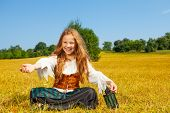 picture of pirate girl  - Laughing girl in costume of pirate sitting on grass and holding a lantern - JPG