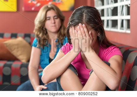 Teenager problems - Sad teenage girl cries with her worried mother on the background