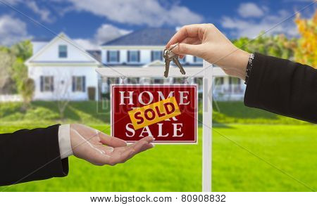 Sold Real Estate Sign and Agent Handing Over Keys to New Home.