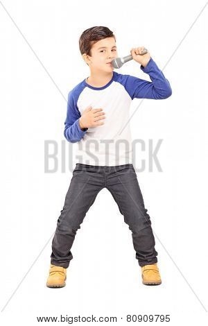 Full length portrait of a joyful little kid singing on a microphone isolated on white background