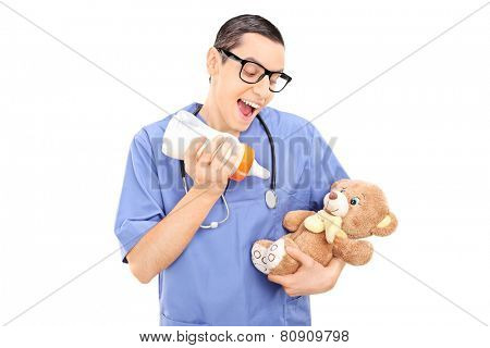 Silly male doctor feeding milk to a teddy bear isolated on white background