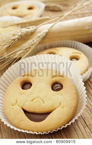 closeup of some smiley biscuits on a wooden worktop with some ears of wheat and a wooden rolling pin