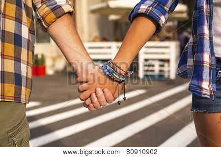 Young couple walking in the City holding hands, close-up.