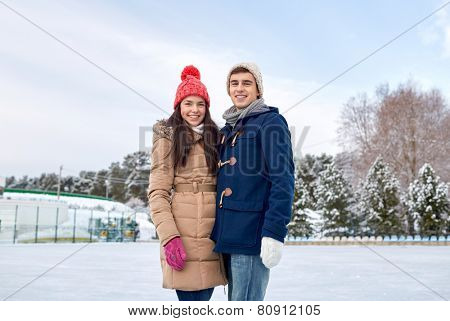 people, winter, friendship, love and leisure concept - happy couple ice skating on rink outdoors