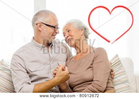 family, relations, love, age and people concept - happy senior couple hugging and holding hands on sofa at home with big red heart shape