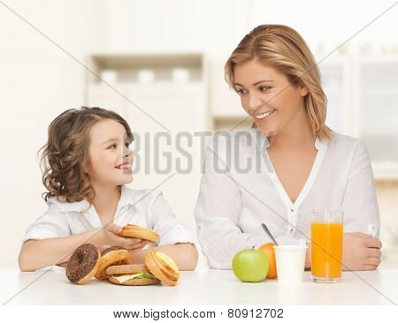 people, healthy lifestyle, family and unhealthy food concept - happy mother and daughter eating different food over home kitchen background