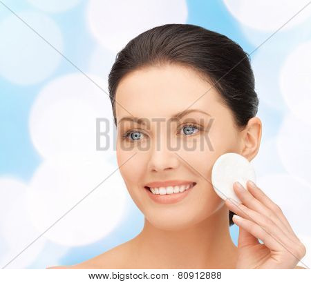 beauty, people and health concept - beautiful smiling woman cleaning face skin with cotton pad over blue lights background
