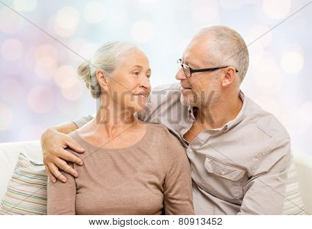 family, relations, love, age and people concept - happy senior couple hugging and looking at each other on sofa over holidays lights background
