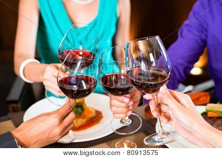 Close up of hands toasting in restaurant