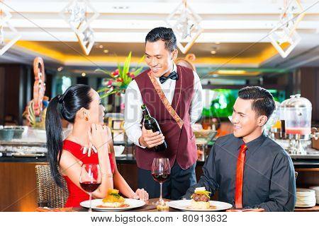 Waiter serving wine in restaurant