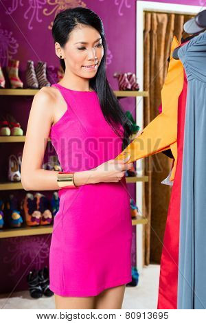 Asian young woman choosing garment in fashion store