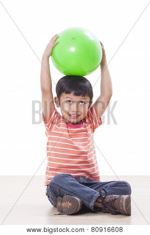 Cute little boy holding head over to the green ball