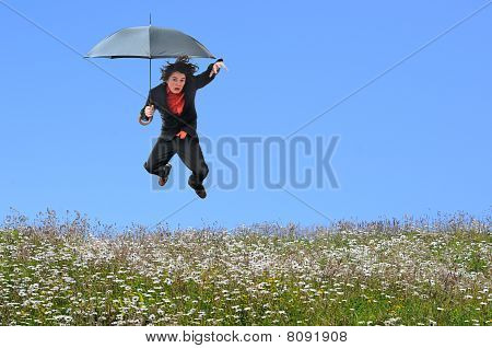 Businessman Jumping Over Grass Hill