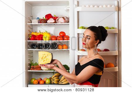 luxurious rich woman with cheese in the hands of the fridge