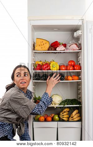 hungry dirty woman stealing food from the fridge