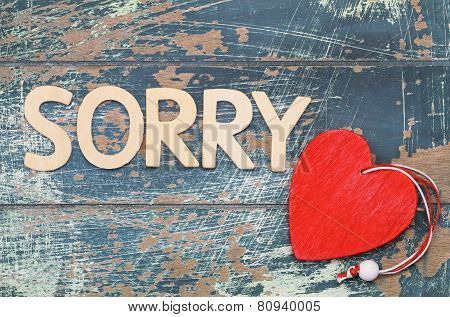 Sorry written with wooden letters on rustic surface, and red wooden heart