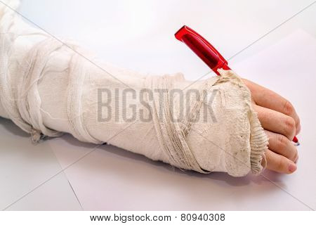 Hand Writing With The Red Pen With Medicine Bandage On Injury Arm
