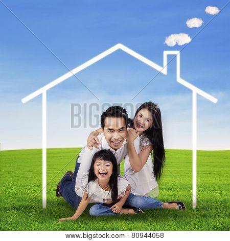 Excited Family With A Dream House At Field