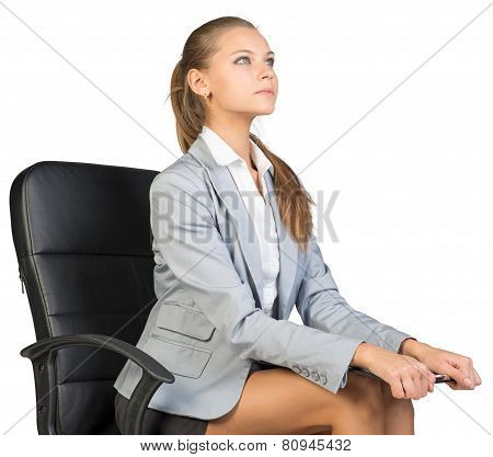 Businesswoman sitting on office chair with clipboard