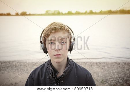 Portrait Of A Teenage Boy With Headphones At A Riverbank, Toned Image