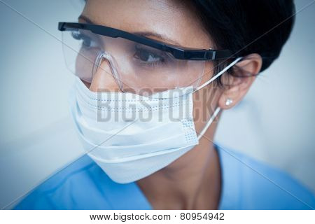Close up of female dentist wearing surgical mask and safety glasses